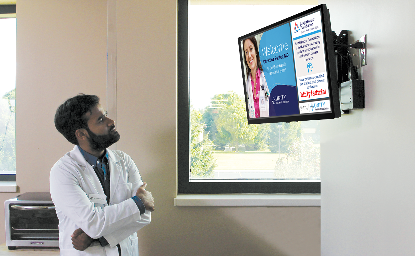 A young male doctor looks at a screen in a break room of his practice with information about neurology clinical trials on it.