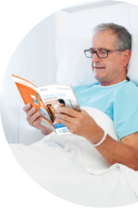 Hospital patient in bed reading a bedside patient guide.