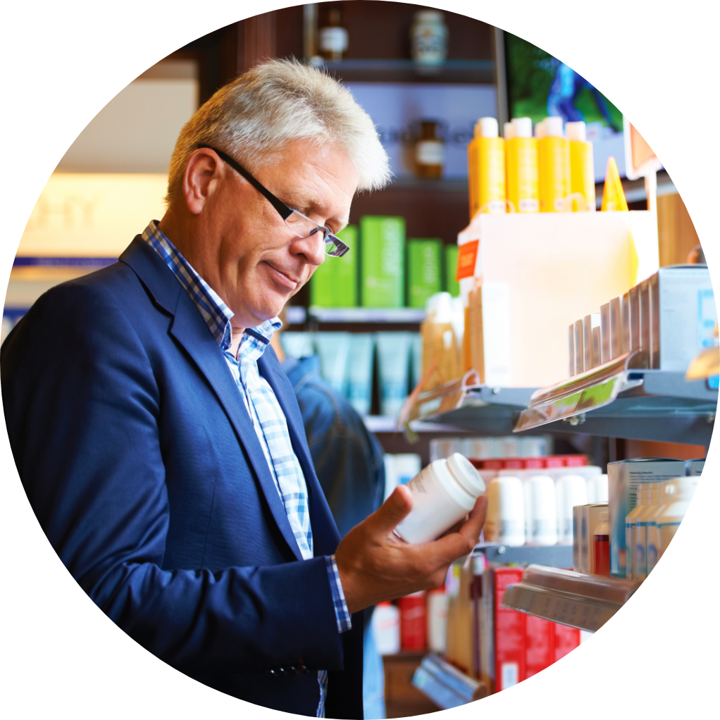 A man examining an OTC medication in the aisle of a pharmacy.