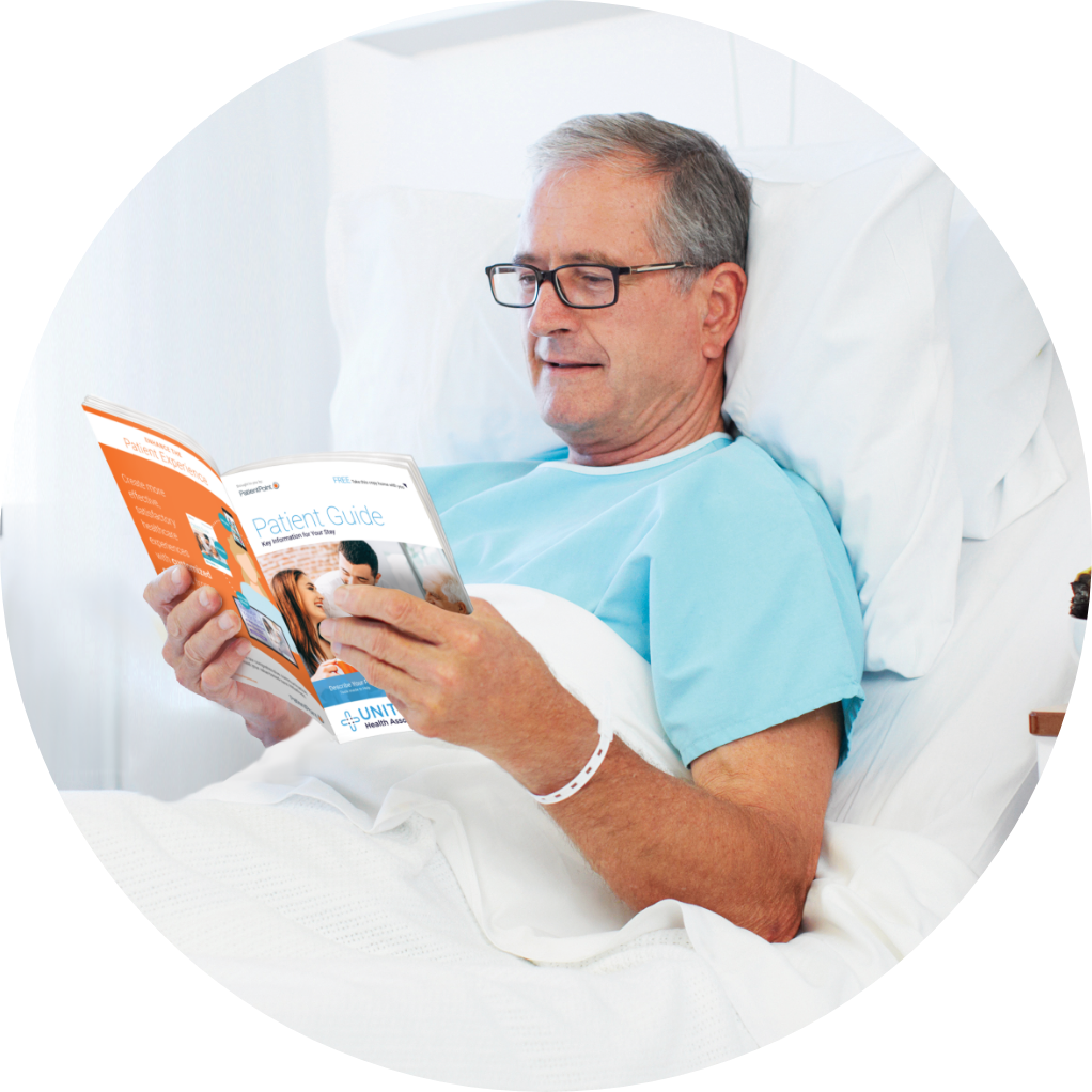 Patient in bed reading a hospital patient guide.