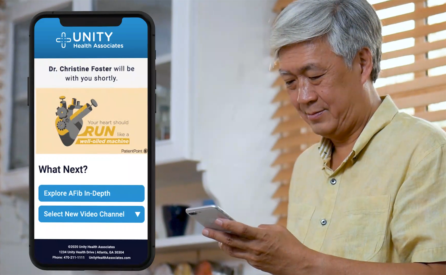 A middle-aged man holds his phone while standing. An image of the phone to the left of the man displays that he is waiting for a telehealth appointment and is watching programming about atrial fibrillation while he waits.