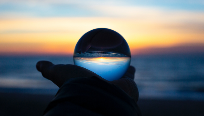 A person holding a crystal ball looking out onto the ocean