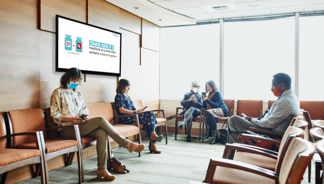 A group of patient sit in a waiting room featuring a digital screen with information about acetaminophen safety.