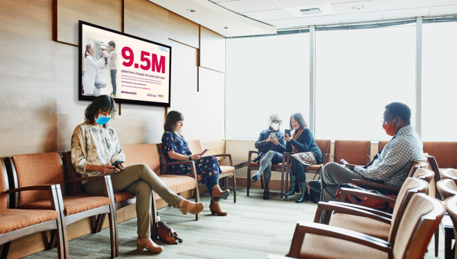A group of patients sit in a waiting room featuring a digital screen with content celebrating physician assistants.