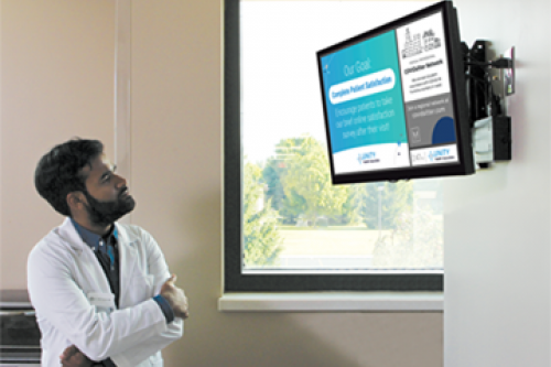 A young doctor looks up at a screen in the break room of the medical practice where he works and sees information about COVIDSitters, a program providing free services to COVID-19 frontline healthcare workers.
