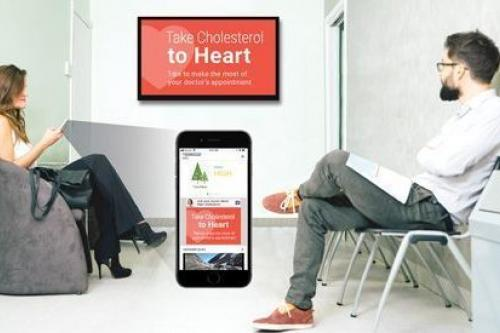 Doctor's waiting room with a woman checking her phone and a man watching a cholesterol PSA on a digital screen. Woman's phone is enlarged to show the same message.