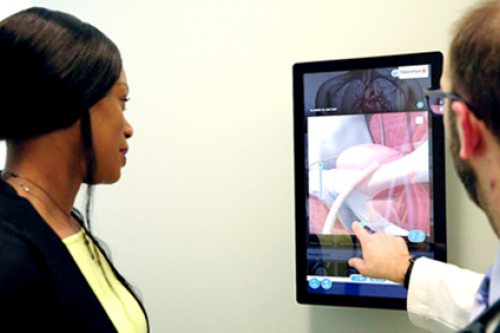 Patient and a doctor explore a digital anatomical model on a PatientPoint interactive touchscreen in the exam room.
