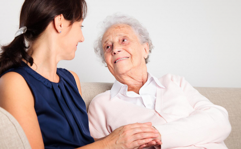 A female caregiver sits with an elderly woman while holding her hand and looking at her.